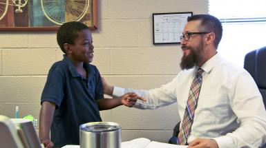 teacher speaking with young student